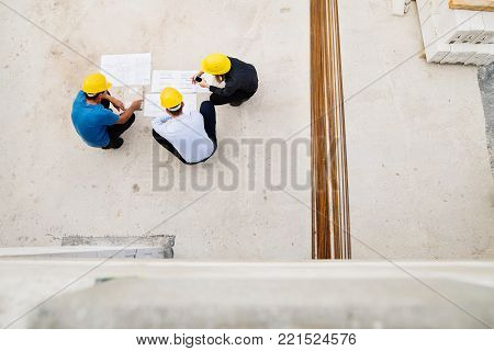 Architect, civil engineer and worker looking at plans and blueprints, discussing issues at the construction site. High angle view.