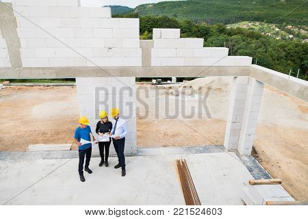 Architect, civil engineer and worker looking at plans and blueprints, discussing issues at the construction site. Aerial view.