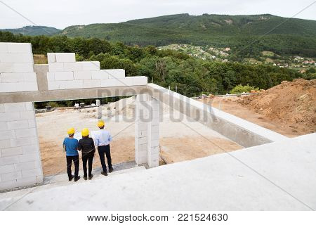 Architect, civil engineer and worker discussing issues at the construction site.