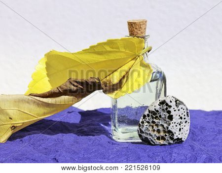 Still life with vintage glass bottle, yellow wilted leaf and small grey pebble stone on the dark blue napkin. Shallow selective focus and place for text.