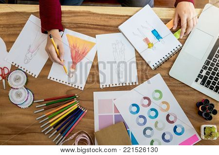 Young woman designer working as fashion designers at work with fashion sketches and color charts, profession and job occupation, Fashion Designer Stylish Concept.