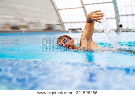Man swimming in an indoor swimming pool. Professional swimmer practising in pool.