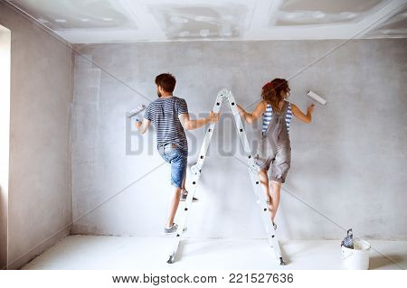 Beautiful young couple at home standing on ladder painting walls in their new house using paint rollers. Home makeover and renovation concept.