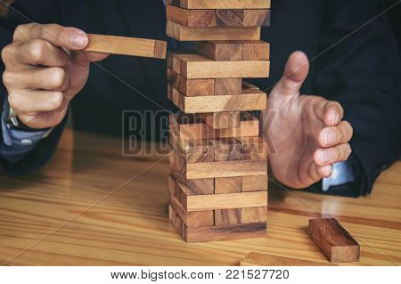 Alternative risk concept, plan and strategy in business, Risk To Make Buiness Growth Concept With Wooden Blocks, Images of hand of businesspeople placing and pulling wood block on the tower.