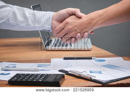 Close-up of two business people shaking hands while sitting at the working place. Two confident executives business colleagues meeting and discussing ideas of project about company offer.
