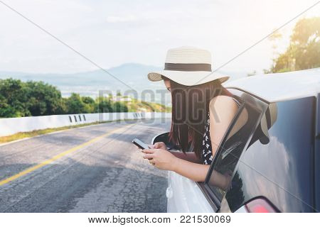 Relaxed happy traveler, Young beatiful asian gilr using smart phone and Reach out of the car at sunset and beautiful view with mountain road background.