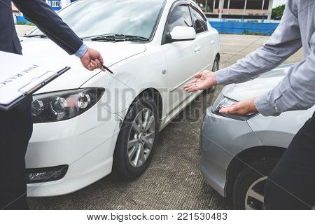 Insurance Agent examine Damaged Car and filing Report Claim Form after accident, Traffic Accident and insurance concept.