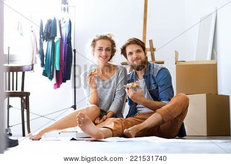 Young married couple moving in new house, sitting on the floor near cardboard boxes, eating pizza.