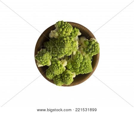 Roman cauliflower in wooden bowl isolated on white background. Roman cauliflower close up. Fractal texture of romanesco broccoli. Roman cauliflower with copy space for text. Top view