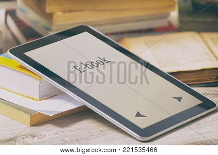 MModern ebook reader on a table with piles of books