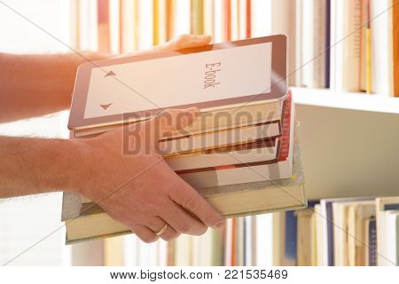 Man holding in hands a modern ebook reader and paper books, bookshelf in the background