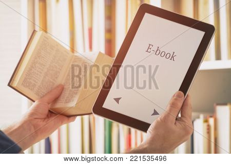 Man holding a modern ebook reader in one hand and paper book in other, books and bookshelf in the background
