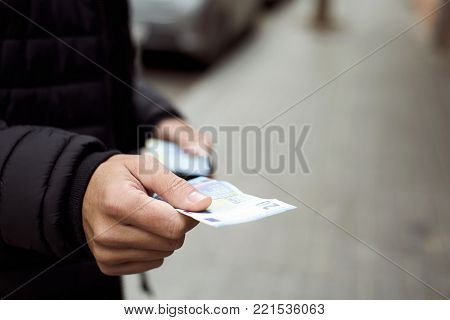 closeup of a young caucasian man on the street with a wad of euro notes in one hand while giving a twenty euro note to the observer