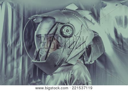 Discover, Boy playing to be an astronaut with space helmet and metal suit over silver background