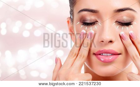 Pretty woman massaging her face, skin treatment antiaging concept. Abstract background with blurred lights
