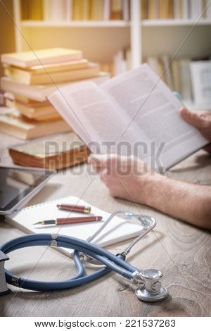 Young doctor is learning and preparing for the exam, he is using books and tablet to search for knowledge