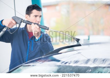 Dedicated young worker washing car manually with high-pressure hose