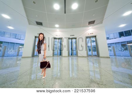 Woman in suit with bag in hall with transparent elevator doors, collage