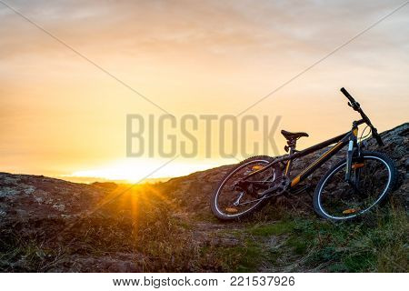 Mountain Bike on the Rocky Trail at Sunset. Extreme Sport Concept. Free Space for Text.
