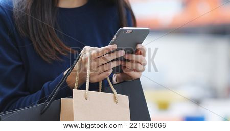 Woman use of smart phone at outdoor with holding shopping bag