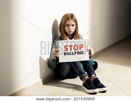 "Sad teenage girl holding ""Stop bullying"" sign indoors poster"