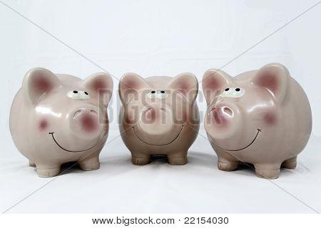 three ceramic piggy banks, pink and smiling
