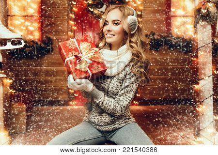 Pretty girl in winter clothes is sitting on the porch of a house decorated for Christmas and holding a gift box. Time for miracles.