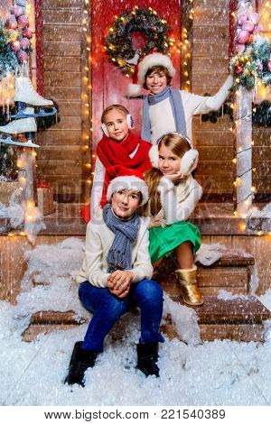 Four cheerful children in winter clothes stand near the house decorated for Christmas. Kid's fashion. Time for miracles. Merry Christmas and Happy New Year.