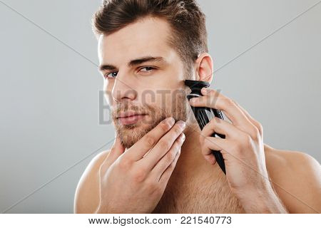 Attractive masculine male being undressed at home having skincare, while shaving his face with trimmer against grey wall