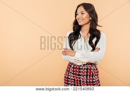 Portrait of a smiling asian woman standing with arms folded and looking away at copy space isolated over beige background