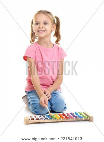 Cute little girl playing xylophone on white background