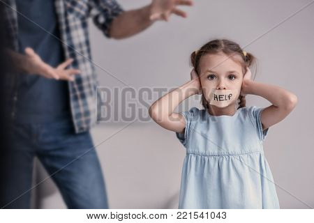 Man scolding his daughter with taped mouth and word