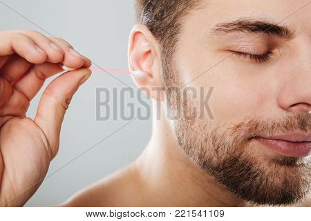 Close up portrait of a young man cleaning his ears with a cotton swab isolated over gray background