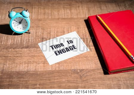 Composition with clock, notebook and phrase TIME TO ENGAGE on wooden background