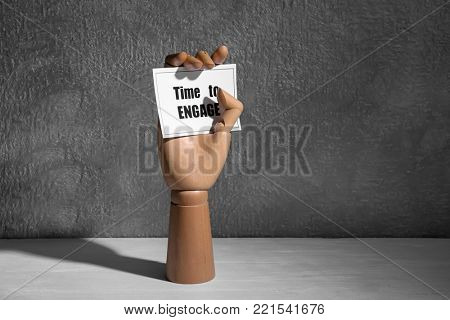 Mannequin hand holding card with phrase TIME TO ENGAGE on table against grey textured background
