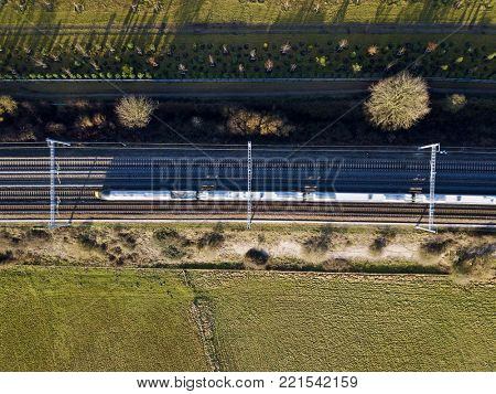 High speed electric passenger train in countryside top down aerial view