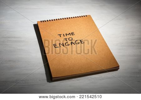 Notebook with written phrase TIME TO ENGAGE on wooden background