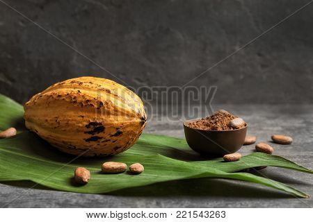 Ripe yellow cocoa pod and bowl with powder on table