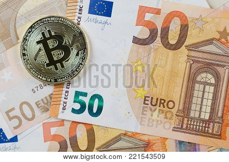 Physical version of Bitcoin, new virtual money . Golden symbolic coin of bitcoin on Euro banknotes. Exchange bitcoin. Concept worldwide cryptocurrency.