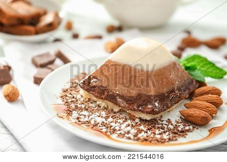 Yummy dessert with caramel and almond on plate, closeup