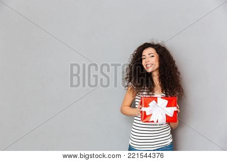Happiness and joy expressing young woman holding gift-wrapped box with white bow, while standing over grey background