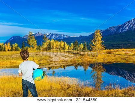 Exquisite Abraham Lake with turquoise water in Canada. Boy in jeans with a globe in his hands admires the lake. Indian Summer in the Rockies. Concept of ecological and active tourism