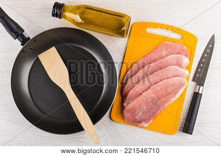 Raw pork schnitzel on cutting board, vegetable oil, frying pan, spatula and kitchen knife on wooden table. Top view