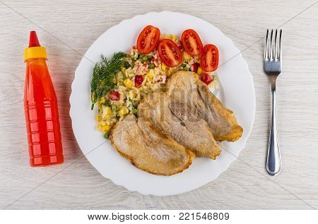 Fried pork schnitzel with vegetable mix, tomatoes, dill in plate, bottle of ketchup and fork on wooden table. Top view