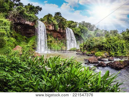 Two rapid waterfalls from the Iguazu Falls in Argentina. Hot tropical sun illuminates the rumbling waterfalls. The concept of extreme and ecological tourism