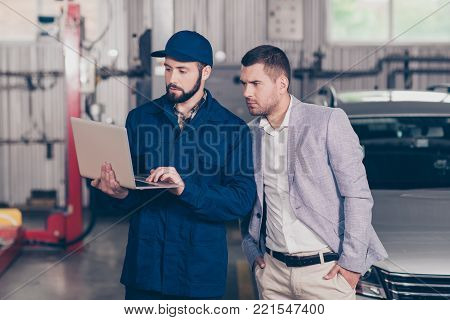 Professional Bearded Mechanic In Safety Blue Overall, Checkered Shirt And Cap Talking, Discussing, G