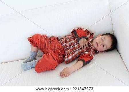Two year old boy fast asleep on a couch