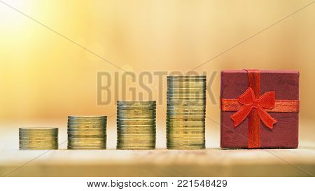 Money savings and spending concept - web banner of golden coins and a red gift box