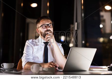 Thoughtful hipster businessman in his office working late at night, sitting at the desk, laptop in front of him.