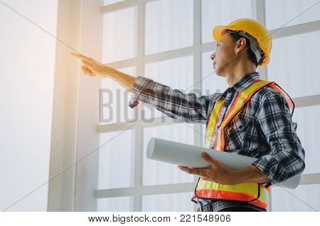 middle aged asian architect, engineer or technician man with safety helmet holding blueprint and pointing finger in construction site building to greeting start up project, business, industry concept